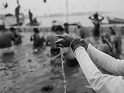A Hindu devotee   lifts her hands in prayer while bathing in the sacred river  during the Kumbh Mela Festival, 2019. Prayagraj, India.