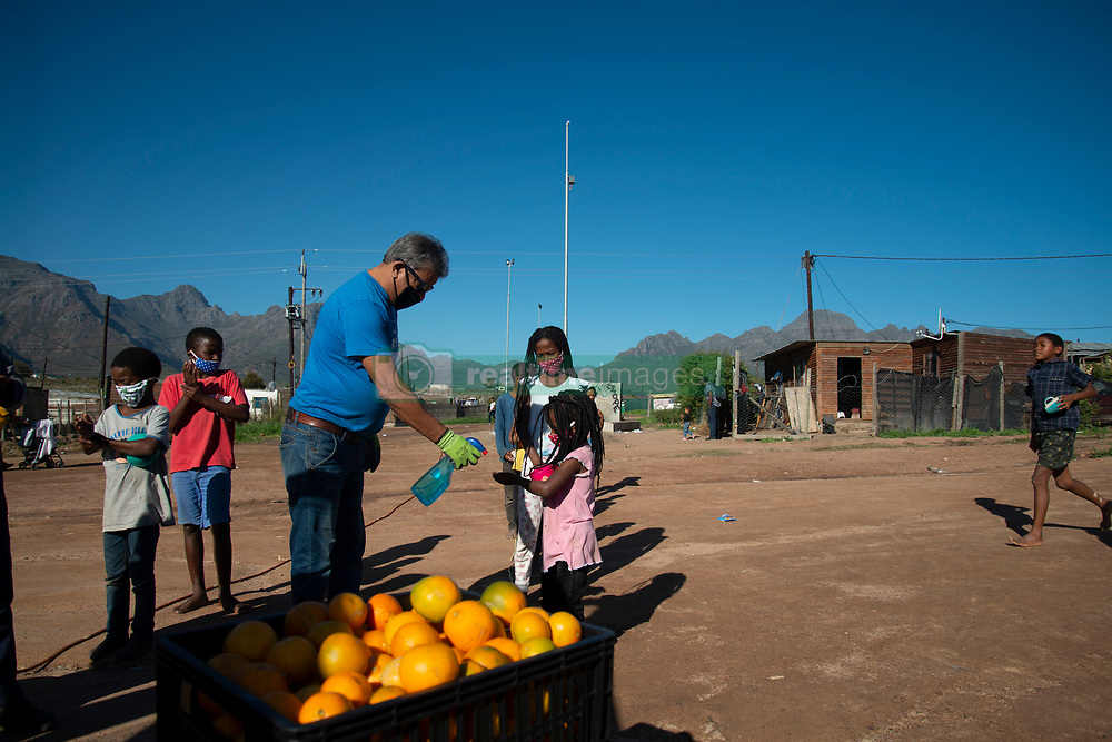 Arnold Okkers helps the kids sanitize their hands at a volunteer food drive in Mountain View, an informal settlement in Jamestown, in the Cape Winelands District, on Saturday, May 29, 2020. It's estimated that most, if not all, of the households here had no income, due to unemployement during lockdown. Cape Winelands is one of the districts in the Western Cape that has been designated a hotspot area, in terms of people testing positive for COVID-19. When South Africa moves down to Stage 3 of the nationwide lockdown on June 1st, hotspots areas will remain under stricter regulation and surveillance, per the latest government announcements. PHOTO: EVA-LOTTA JANSSON