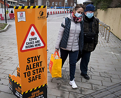 © Licensed to London News Pictures. 01/02/2021. Woking, UK. Members of the public wearing face masks walk past a Coronavirus alert sign in Woking town centre in Surrey, where a South African variant of Covid-19 has been found. Photo credit: Ben Cawthra/LNP