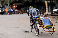 Myanmar/Burma, Mandalay. Trishaw driver on the street in Mandalay. <br /> In Myanmar, trishaw passenger don't ride behind the driver, but with him - back-to-back ( one of the passengers is facing forward, and the other one backward).
