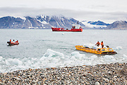 A Soviet-era amphibious vehicle is used to shuttle gasoline from a delivery ship to the storage tanks on land at the Polish Polar Station in Hornsund, Svalbard. The station operates year round and uses 90,000 liters of gasoline per year to operate generators, boats, snowmobiles, and heavy machinery.