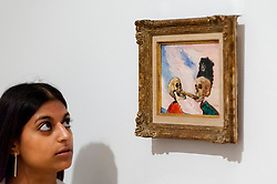 """© Licensed to London News Pictures. 25/10/2016. London, UK. A staff member views """"Skeletons Fighting over a Pickled Herring, 1891"""" at the preview of Intrigue: James Ensor by Luc Tuymans.  Curated by fellow Belgian artist Luc Tuymans, this is the first exhibition of work by modernist artist James Ensor (1860-1949) to be held in the UK in twenty years and will run 29 October 2016 to 29 January 2017. Photo credit : Stephen Chung/LNP"""