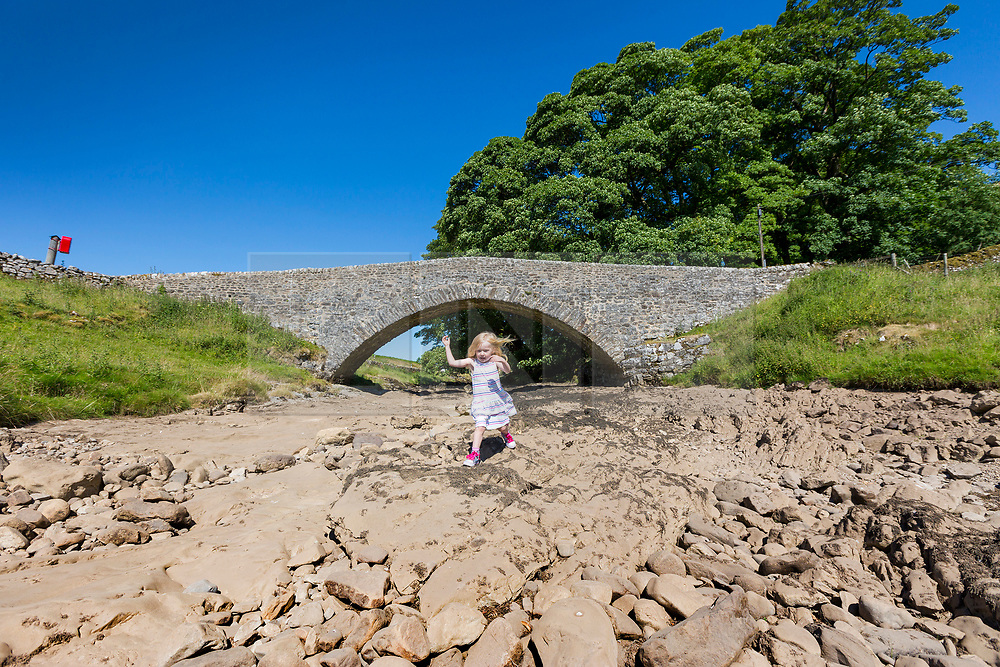 © Licensed to London News Pictures. 03/07/2018. Yockenthwaite UK. Three year old Scarlet plays on the dried up river bed of the River Wharfe in the village of Yockenthwaite, Yorkshire Dales, as the UK heatwave continues & a hosepipe ban looks imminent. Photo credit: Andrew McCaren/LNP