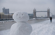 Heavy overnight snowfall covers London in a thick blanket of fine snow. The heaviest snowfall in decades. A showman on the river walk stands in front of Tower Bridge.