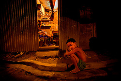 Tanya, 7,  waits for her mother finishing with her customer at brothel in Faridpur, Bangladesh.