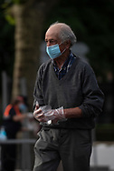 An elder man wearing protective face mask, puts on some plastic gloves. Irun (Basque Country). May 09, 2020. As the downscaling progresses, there are more and more businesses and commercial activities that take over their activity, after having been closed due to the blockade ordered by the Spanish government to prevent the spread of the COVID-19. (Gari Garaialde / Bostok Photo)