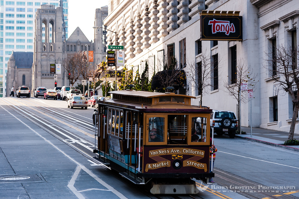 United States, California, San Francisco. Cable car on Nob Hill. Grace cathedral in the background.