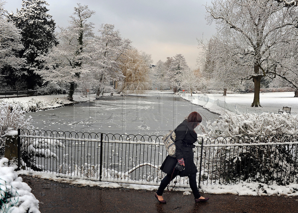 © Licensed to London News Pictures. 10/02/2012, London, UK. A woman walks past the frozen water course. People enjoy the snow in the grounds of Chiswick House in West London today 10 February 2012. Chiswick House, undergoing restoration,  is the first and one of the finest examples of neo-Palladian design in England.  Inspired by the architecture of ancient Rome and 16th Century Italy, the third Earl of Burlington built the house as a homage to Renaissance architect Palladio.The cold weather across the UK is set to continue over the weekend.  Photo credit : Stephen Simpson/LNP