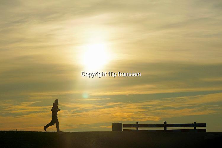 Nederland, Nijmegen, 10-12-2020  Een hardloper traint op de dijk bij een laagstaande zon .Foto: ANP/ Hollandse Hoogte/ Flip Franssen