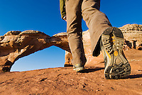 Hiker approaches Broken Arch, Arches National Park, Utah