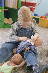 Young boy with Cerebral Palsy playing with dolls on Children's ward in hospital,