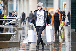 © Licensed to London News Pictures. 02/12/2020. Manchester, UK. A man carries shopping bags in Manchester as the city enters Tier 3 restrictions.  Photo credit: Kerry Elsworth/LNP