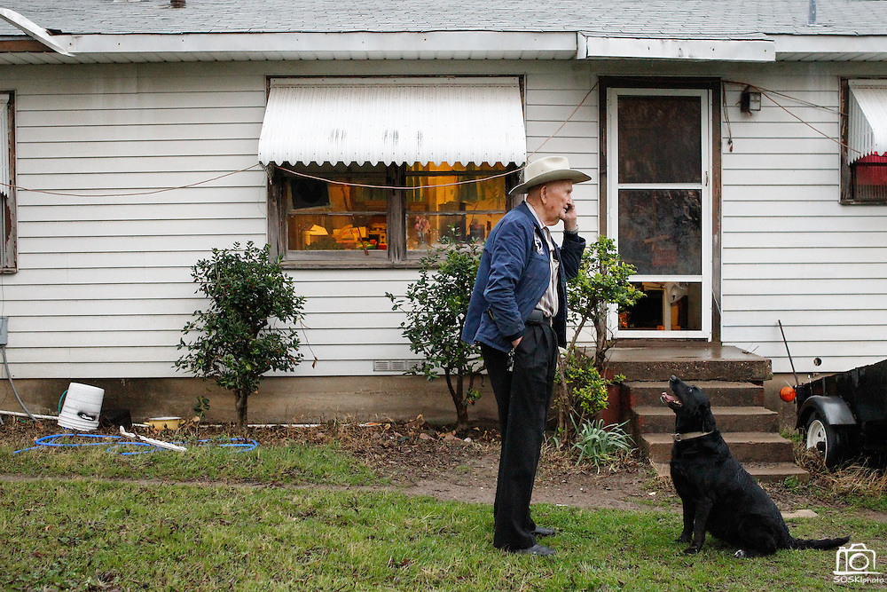 Billy J. Preston, a retired World War II US Naval Amphibious Forces, talks with his daughter on the phone about damage caused by a small tornado with his dog Molly by his side at his home in Dallas, Texas, on January 29, 2013.  (Stan Olszewski/The Dallas Morning News)
