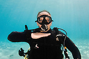 "Underwater Hand signs scuba diver demonstrates the sign language for divers. I'm out of air: ""Cutting"" or ""chopping"" throat with a flat hand"