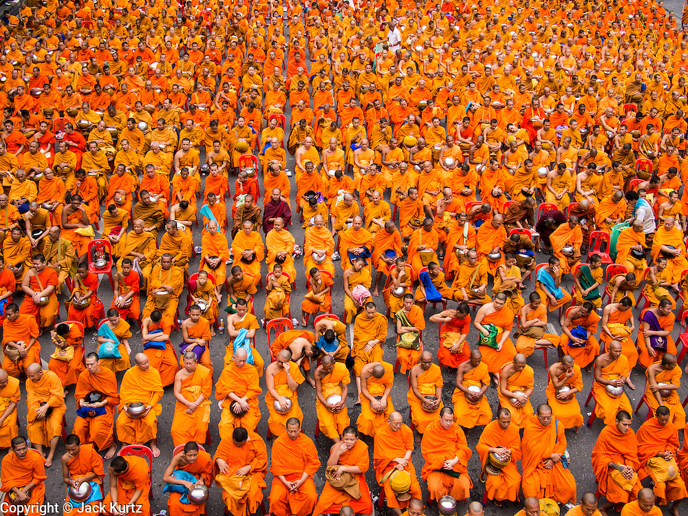 08 SEPTEMBER 2013 - BANGKOK, THAILAND: Buddhist monks pray during a mass alms giving ceremony in Bangkok. 10,000 Buddhist monks participated in a mass alms giving ceremony on Rajadamri Road in front of Central World shopping mall in Bangkok. The alms giving was to benefit disaster victims in Thailand and assist Buddhist temples in the insurgency wracked southern provinces of Thailand.       PHOTO BY JACK KURTZ