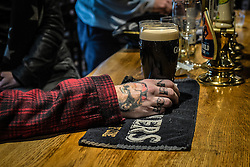 A customer's tattooed hand holds a pint of stout in a traditional English pub in Essex.