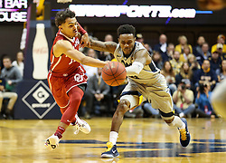 Jan 6, 2018; Morgantown, WV, USA; Oklahoma Sooners guard Trae Young (11) and West Virginia Mountaineers guard Daxter Miles Jr. (4) dive for a loose ball during the first half at WVU Coliseum. Mandatory Credit: Ben Queen-USA TODAY Sports
