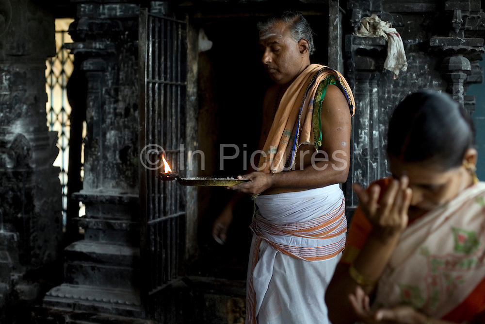 A priest by a shrine at the Murugan temple, gives ritual blessings to pilgrims in Swamimalai, India.