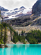 Beautiful, remote Lake O'Hara, with Seven Veils Falls in the trees, in Yoho National Park, near Field, British Columbia, Canada