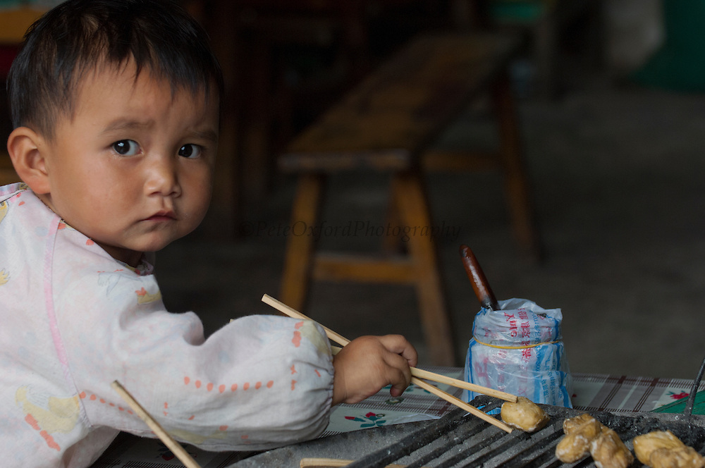 Chinese child eating with chopstix from a very early age.  Yunnan Province. CHINA
