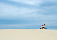This shot was taken on a sand dune in the Outer Banks, NC. The people are getting ready to fly a kite.