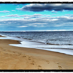 A boy walks on the beach in Plum Island, Massachusetts. Parker National Wildlife Refuge.
