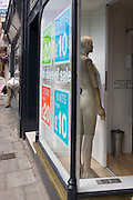 Bending shop owner and mannequin in Bristol's Clifton district clothing shop window.