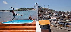 Crianças brincam em  uma piscina depois que a polícia invadiu a casa do traficante chefe da favela do Morro do Alemão em 28 de novembro de 2010 no Rio de Janeiro, Brasil. Após dias de preparação, forças de segurança do Brasil, lançaram um ataque contra uma favela, onde entre 500 e 600 traficantes de drogas estão escondidos e recusam a se render. Cerca de 2.600 tropas aerotransportadas, marines e membros das unidades de elite da polícia participavam da operação como alvo um grupo de favelas sem lei conhecido como Complexo de Alemão. FOTO: Jefferson Bernardes/Preview.com