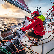 Leg 6 to Auckland, day 07 on board MAPFRE, Blair Tuke trimming at the sunset. 13 February, 2018.