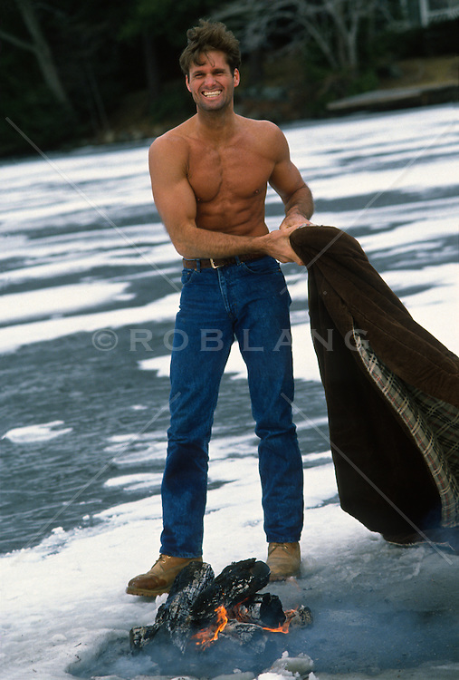 man without a shirt standing on a frozen lake with a bonfire