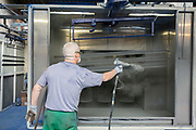 A prisoner powder coating metal bars in the steel industries workshop of HMP Coldingley. Surrey, United Kingdom. HMP Coldingley is a category C training prison, focussed on the resettlement of prisoners. All inmates must work a full working week, within the prison grounds. (Photo by Andy Aitchison)