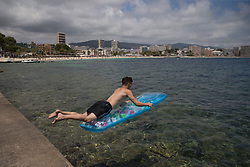 © Licensed to London News Pictures.  29/06/2021. Magaluf, Spain. Mostly A boy jumps into the water in Magaluf. Balearic Islands will go on the UK 'green list' from tomorrow, 4am. Prime Minister of Spain, Pedro Sanchez announced the new rules for Brits coming to Mallorca, Ibiza and other Balearic Islands. Brits willing to visit must have show a proof of vaccination or negative PCR test. Photo credit: Marcin Nowak/LNP
