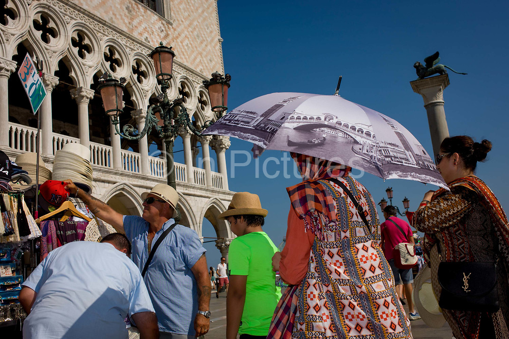 Tourists with umbrellas at the Doge's Palace in Piazza San Marco, Venice, Italy. The wide expanse of Piazza San Marco is in the heart of Venice and where, for most daylight hours, the pavement is crowded with humanity as the influx of tourists who, in their own way, flood the narrow streets with sun-shading umbrellas and the smaller canals with gondolas. Venice attracts 22-million visitors each year (for a city of only about 60,000 residents) while the cultural protection organisation, Italian Nostra, warns that Venice can only accommodate about 33,000 visitors per day but currently at least 60,000 daily.