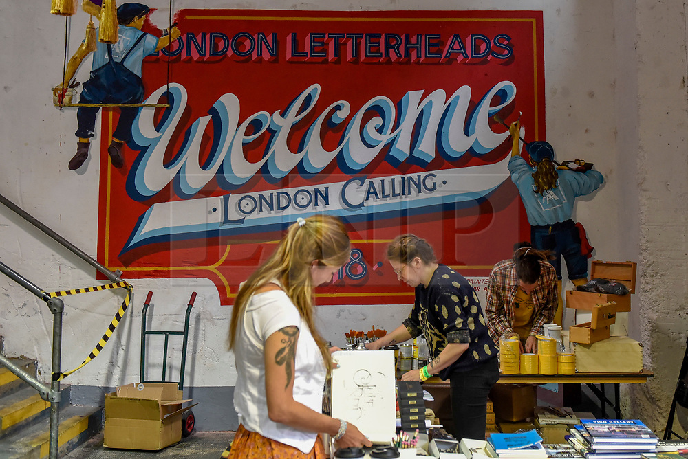 """© Licensed to London News Pictures. 17/08/2018. LONDON, UK. A handpainted welcome sign greets visitors to """"Letterheads 2018: London Calling"""", an international gathering of professional sign writers and lettering artists from over 30 countries.  The event is taking place at the Bargehouse, Oxo Tower Wharf in central London untikl 19 August.  Photo credit: Stephen Chung/LNP"""