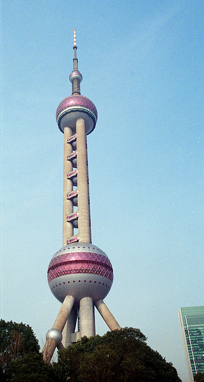 The Pearl Tower stands tall above the trees and other towers in Shanghai, China.
