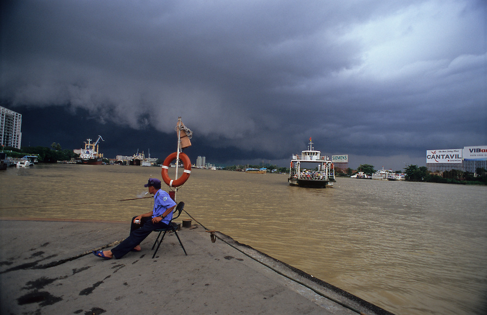 A storm rolls in to the east of Ho Chi Minh City during the rainy season. At the saigon river ferry entrance, a security guard smokes a cigarrette and waits to guide the on coming motorbikes onto the ferry which takes passengers across the river from district 1 to district two. 2007.
