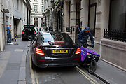 A bike courier squeezes past a black Mercedes in a narrow lane in the City of London, the capitals financial district, founded by the Romans and whose small lanes still date from medieval times, before the Great Fire of London in 1666, on 4th February 2020, in the City of London, England.