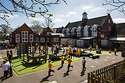 Children enjoying their playtime outdoors in the playground of South Farnborough Infant School, Hampshire, UK.   Children are running around and playing games in the sunshine.