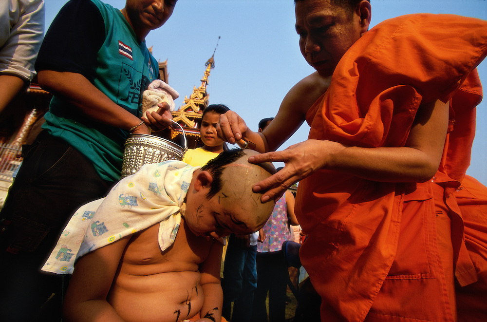 A monk shaves the head of a Shan boy during Poy Sang Long, a yearly ceremony at which boys are ordained as novice monks, Mae Hong Son, Thailand. The shaving takes place inside the Buddhist temple Wat Hua Wiang. Practically every Shan boy goes through this three-day ceremony sometime between the age of eight and fourteen. After the ordination, the boy spends about one month in a Buddhist monastery and then usually returns to normal life again.