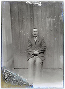 portrait of man sitting in front of barn door eroding glass plate