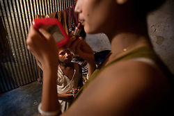Suma, 8, looks at Shetu, 17, herself in a mirror at brothel in Tangail, Bangladesh. Her mother is a sex worker.