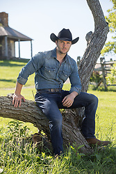 hot cowboy sitting on a tree branch at a beautiful ranch