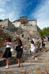 Worshipers leaving the Panayia Glykofilousa church(Virgin Mary of the Sweet Kiss) perched on a hill above Petra on Lesvos Island in Greece