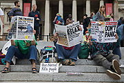 Environmental activists from Extinction Rebellion read replica newspapers bearing climate-based headlines in Trafalgar Square during the first day of Impossible Rebellion protests on 23rd August 2021 in London, United Kingdom. Extinction Rebellion are calling on the UK government to cease all new fossil fuel investment with immediate effect.