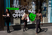 Topless black man with bulging muscles walks past women shoppers in central London. Posing as he walks, the male walks past the females with biceps and pecs rippling in the sunshine. Such egotism seems everyday as the women hardly seem to notice his athletic presence. Either that or they're ignoring the eccentricity.