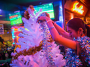 "17 DECEMBER 2013 - BANGKOK, THAILAND:    A worker in a ""go-go"" bar strings Christmas light on a tree in front of bar on Soi Cowboy in Bangkok.   PHOTO BY JACK KURTZ"
