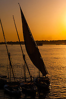 Luxor, Egypt. The sun sets over the Nile. Feluccas on the East Bank.