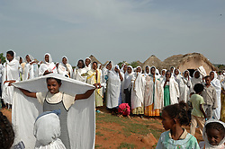 """Coptic christians pray outside St. Mary's church in the village of Fithi which means """"justice"""" on the outskirts of  Barentu, Eritrea August 27, 2006. During this ceremony, Tiblits neighbor Zaid Tesheme, 31 had her baby baptized with the name Mihreteab. The donkey that Tiblets received from the womens union """"Hamade"""", helped them prepare for the celebration afterwards."""