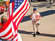 "25 MAY 2010 - PHOENIX, AZ: A woman carries an American flag in front of US Airways Arena in Phoenix, May 25. People opposed to illegal immigration and in favor of Arizona SB1070 picket the Phoenix Suns playoff game against the Los Angeles Lakers Tuesday. About 10 people attended the protest. One person opposed to SB1070 held a counter demonstration. SB1070 makes it an Arizona state crime to be in the US illegally and requires that immigrants carry papers with them at all times and present to law enforcement when asked to. People are picketing the Suns games because Suns owner Robert Sarver has expressed opposition to the law and has had the Suns wearing jerseys that say ""Los Suns.""  PHOTO BY JACK KURTZ"