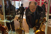 A man looks at violins in a display case. The Chamber of Commerce of Cremona showed many antique and valuable string instruments from Cremonese makers.